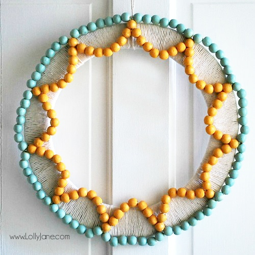 Such a fun handmade wood bead wreath! Learn how to make this wreath with beads, paint and a little time to craft! #beadwreath #handmadewreath #woodbeadwreath #howtomakewoodbeadwreath #wreathtutorial