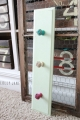 Make cute hooks by screwing fun knobs into a repainted cupboard door, easy! #diy #hooks #knobs