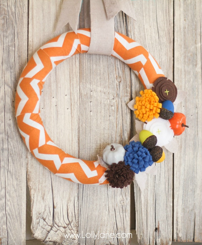 DIY Fall wreath tutorial. Love these felt flowers and painted pumpkins to create this pretty fabric fall wreath! #falldecor #fallwreath #falldecorations #chevronwreath #acorndecor