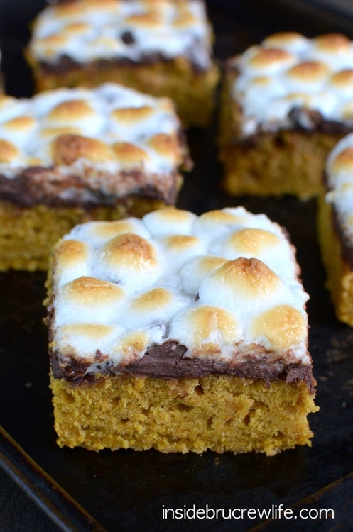 Pumpkin S'mores Bars: Spicy pumpkin cake bars topped with melted chocolate and gooey marshmallows are the perfect dessert for bringing summer into fall. #falldessert #fallrecipe #pumpkinbars #pumpkindessert #pumpkinsmores #smoresbars #smoresdessert #fallrecipe #falldessert
