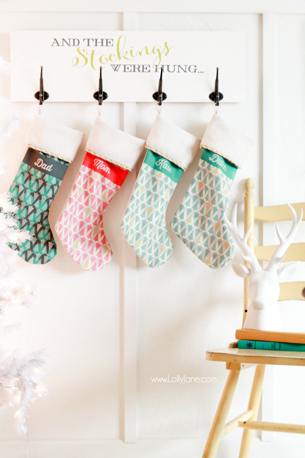 Stenciled Wall Mounted Stocking Holder Board - Tutorial via Lolly Jane - Easy DIY Christmas Stocking Holder Board, perfect for fireplace mantle-less spaces!