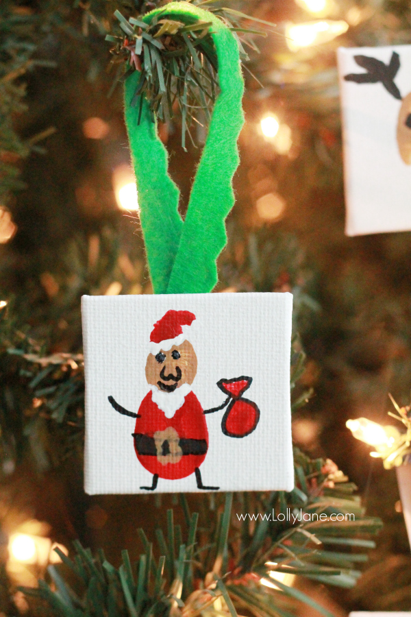 ADORABLE mini canvas thumbprint ornaments! SO EASY to make, kids have fun crafting and you get a Christmas keepsake for years to come. Great Christmas kids craft and Christmas gift idea! Love this Santa thumbprint ornament!