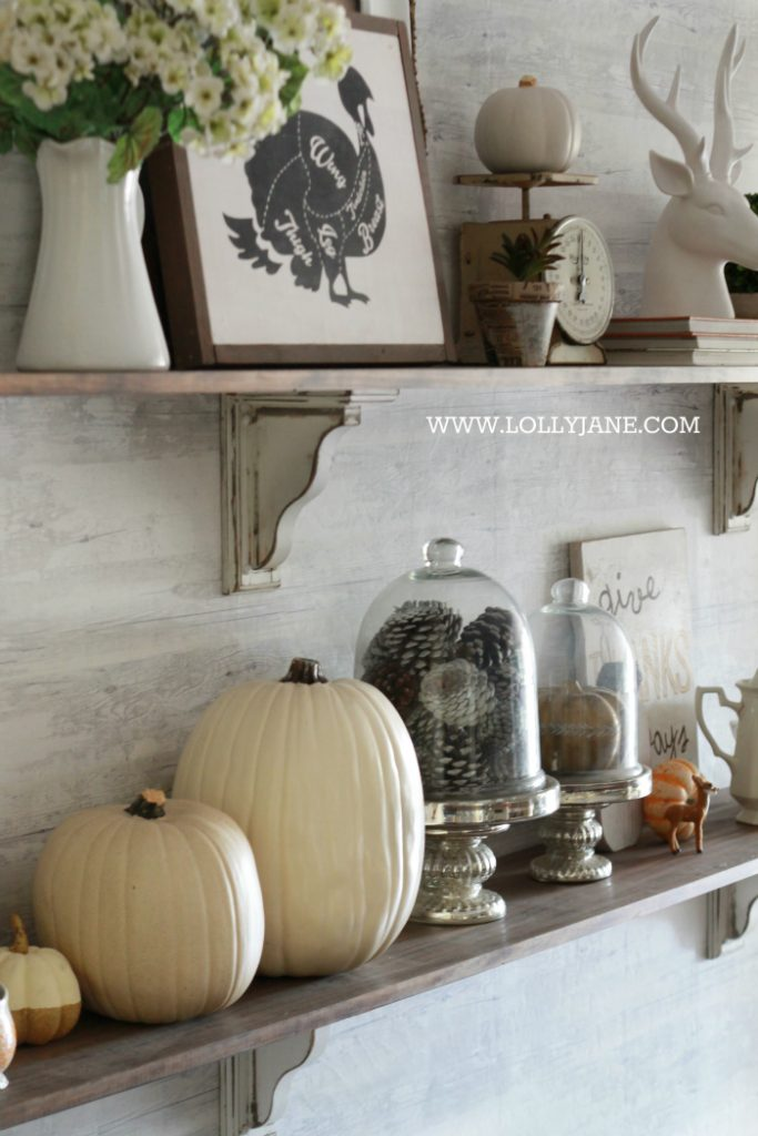 Beautiful farmhouse Thanksgiving dining room decorations. Decorate the table and shelves in layers of pumpkins and signs, fill in with greenery, books and pinecones. Cute Thanksgiving decor ideas that you can easily copy!