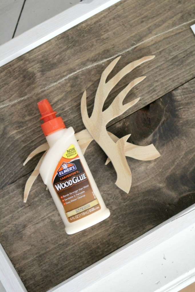 Learn how easy it is to make this rustic DIY wooden antler frame. Cute wall decor idea!