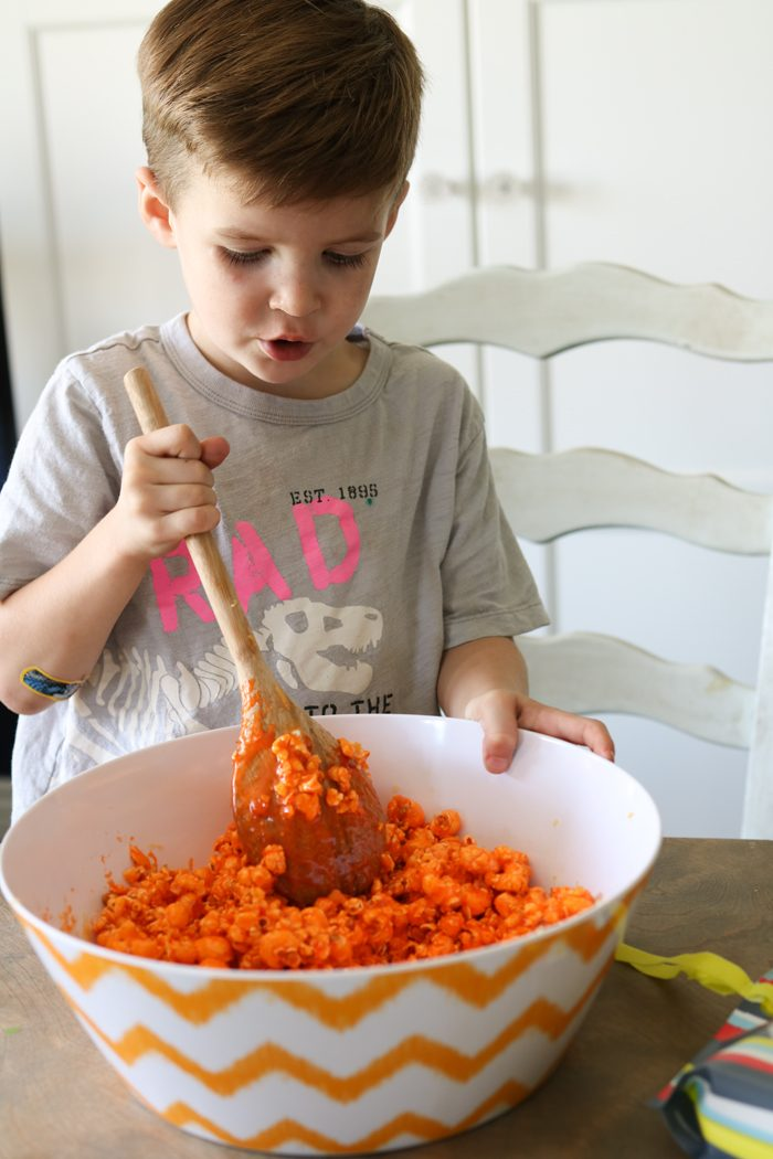 Easy and YUMMY Candy Covered Halloween Popcorn! Perfect for little hands to help in the kitchen, then bag up for a spooky treat!