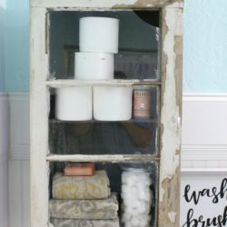DIY Bathroom Cabinet - How to install a bathroom cabinet on the wall. We used an old trunk insert and a vintage window to create a chippy but sturdy bathroom cabinet. Love this farmhouse bathroom! Such a fun bathroom cabinet diy!