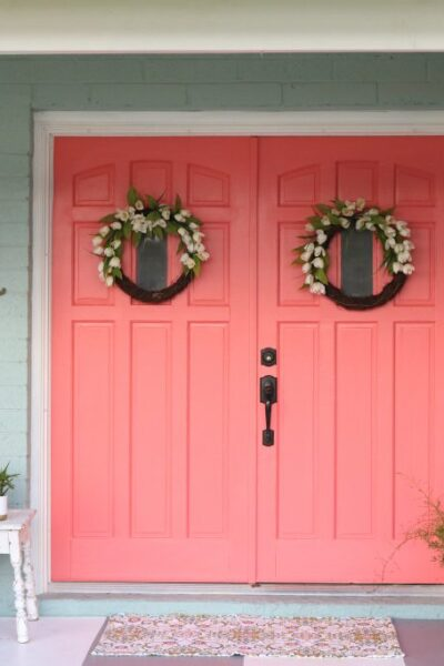 Loving these bright painted coral front doors! So easy to make a statement with bold front door paint choices using @decoart's Curb Appeal paint. Such cheery front doors on a colorful porch. Cute outdoor decor ideas!