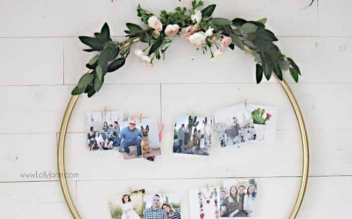 Looking for creative ways to display family pictures? This <strong>DIY Hula Hoop Photo Display</strong> is so easy to make. We love the gold accents and faux florals and you'll love how easy it was to put together. #hulahoophack #photodisplay #weddingidea #diyweddingphoto #photodisplayideas