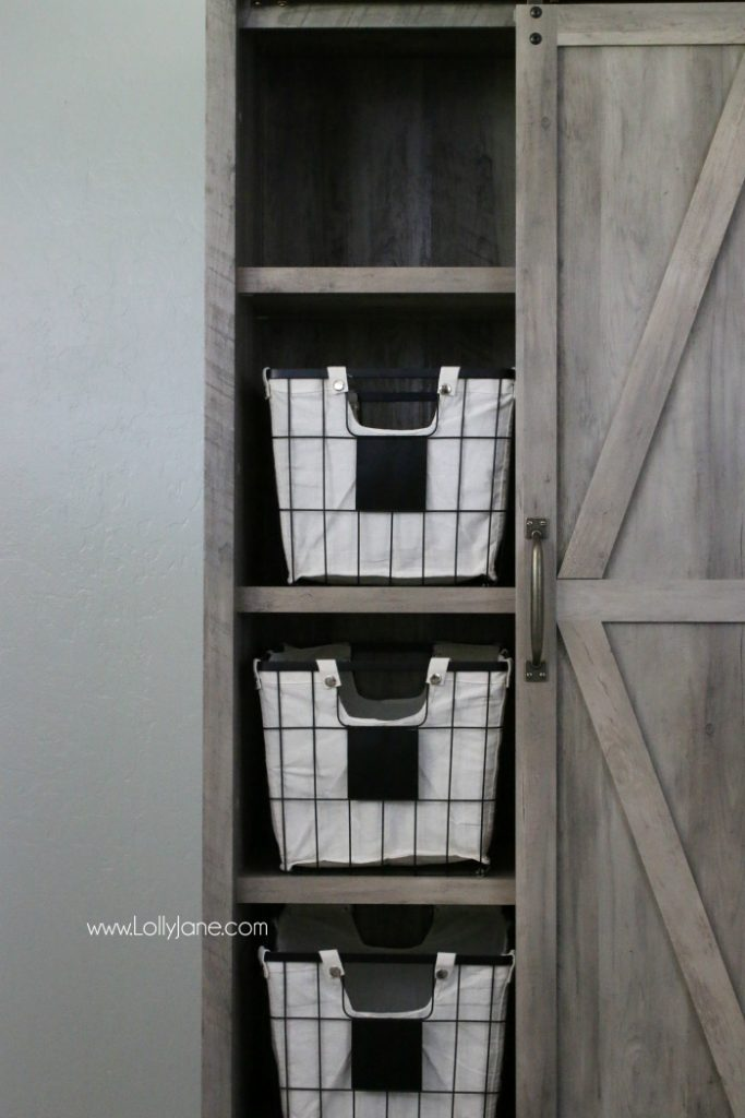 Love this farmhouse cabinet with these chalkboard wire baskets. Such cute laundry room decor!