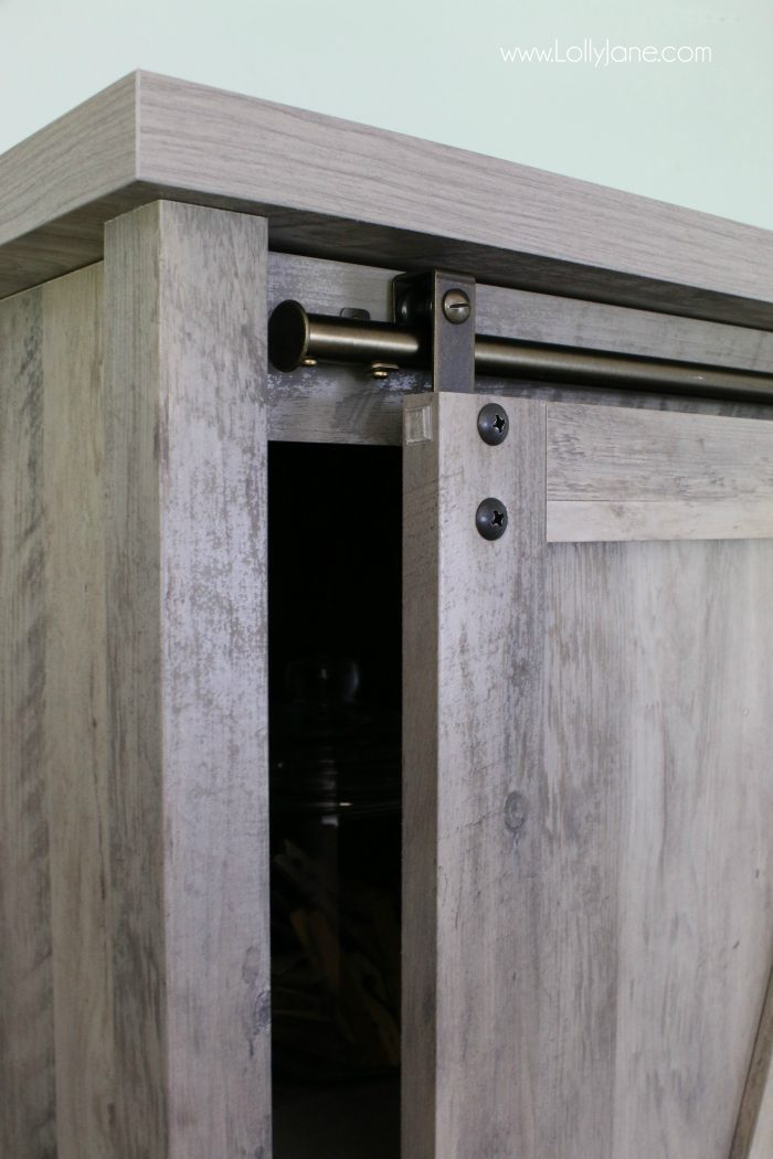 This sliding barndoor farmhouse cabinet is so cute! Love this modern farmhouse decor, completes this laundry room makeover so well!