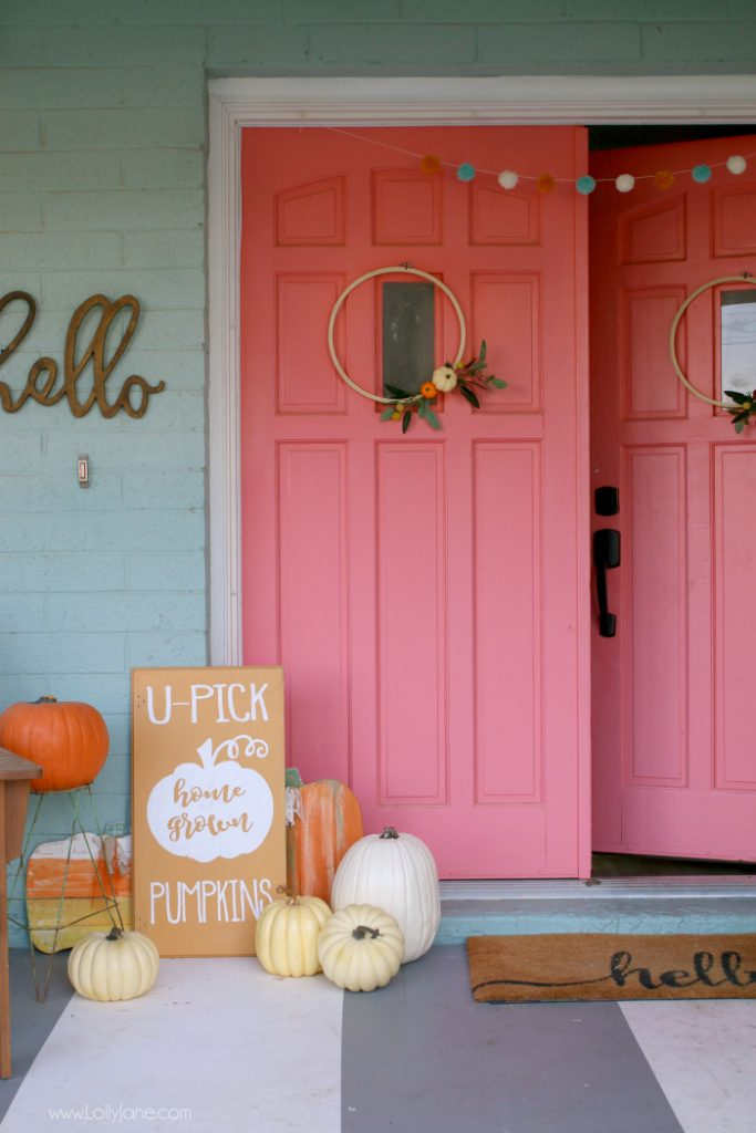 These coral doors make a big statement on this farmhouse, love the pile of pumpkins at the door!