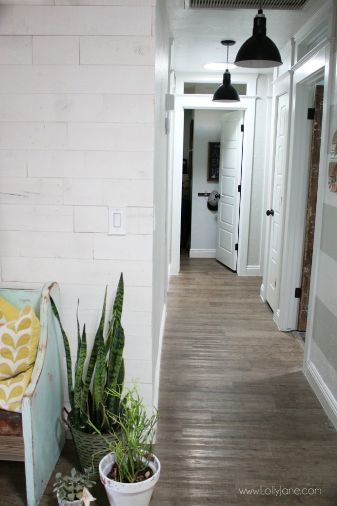 Such a pretty farmhouse hallyway with shiplap walls and pretty barn light pendants!