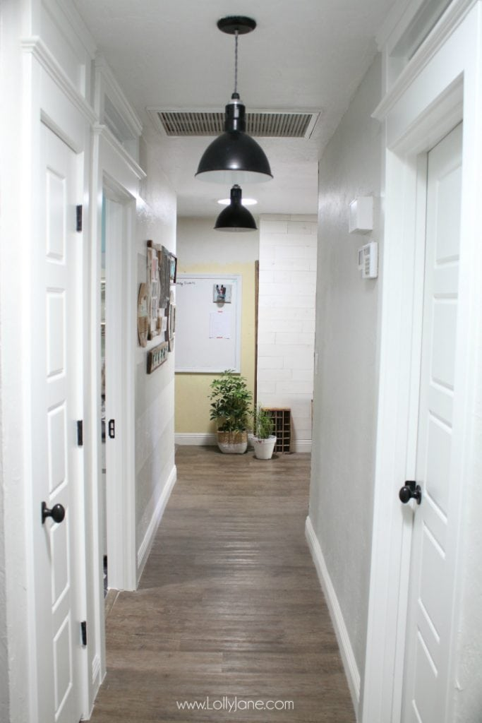 Love this farmhouse hallway makeover. The raised ceilings, black barn light pendants and transom windows add so much character to this old house makeover.