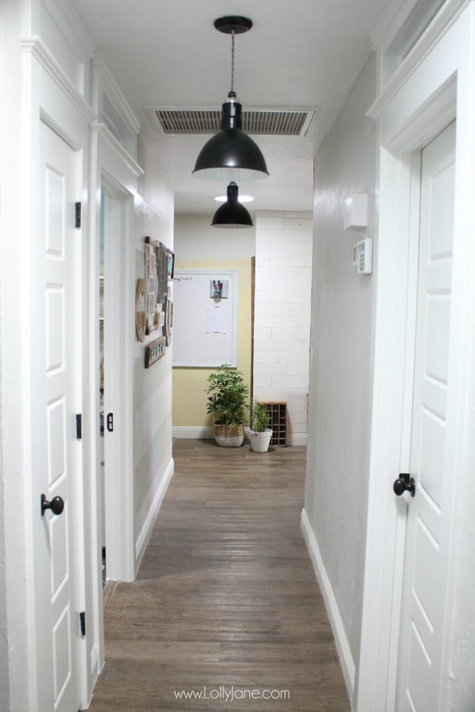 Love this farmhouse hallway with the white trimwork, transom windows and pretty wood wall treament!