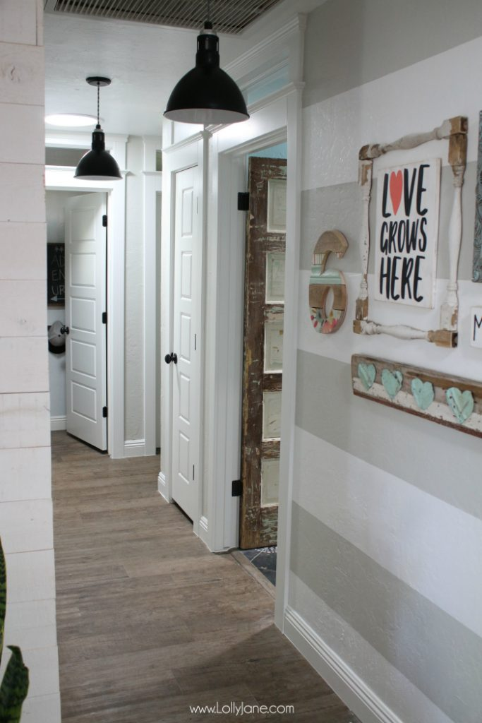 Farmhouse hallyway makeover: love these five panel doors, stripe hallway gallery wall, pendant lighting and an old chippy door for the bathroom!