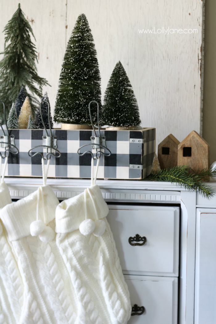 How to make a wooden stocking holder. Paint it in buffalo check for pretty Christmas farmhouse style! Love these bottle brush trees and Magnolia wood houses!