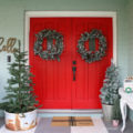 Pretty Christmas front porch decor ideas. Lots of greenery, signs and cheer to this old farmhouse Christmas porch!