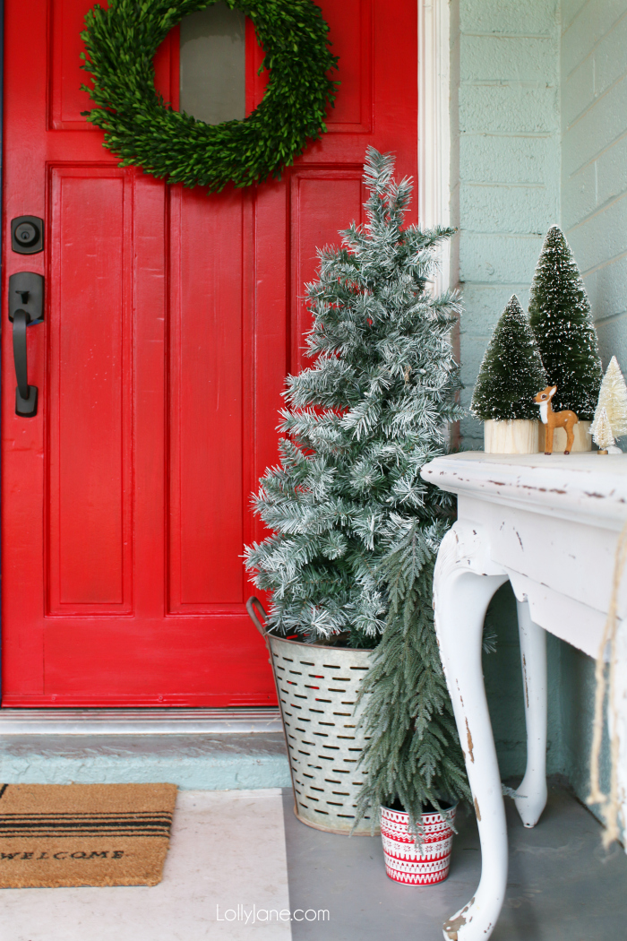 Looking for festive outdoor Christmas decorations? We've gotcha covered with this pretty front porch Christmas decor. From olive bucket trees to a freshly painted cherry red door, we've got all the tips and tricks to deck your front porch out for the holidays!