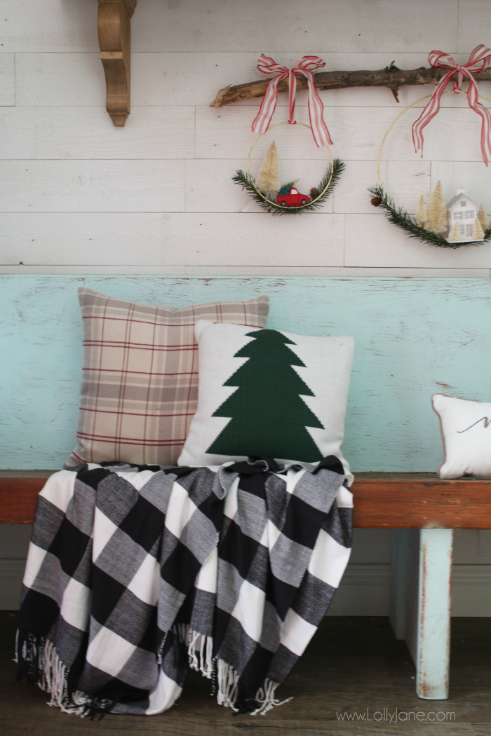 Loving this cozy buffalo check blanket Christmas decor. This fun pine tree Christmas pillow is super fun with these hanging wreaths on a branch.