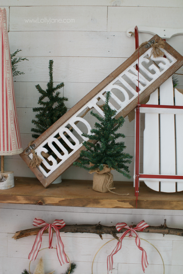 Love this good tidings wood sign Christmas decor. Such a pretty Christmas mantel with natural items like fresh greens and old buckets with new signs and a pretty sled!