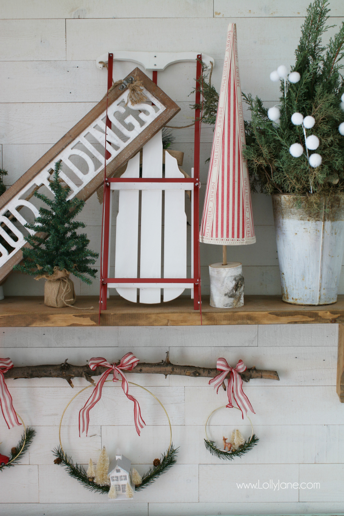 Red and white farmhouse Christmas mantel decor | Love this cheery Christmas mantel with a sled, good tiding sign, DIY Christmas trees and old buckets filled with fresh greens. Such cute holiday mantel decor ideas!