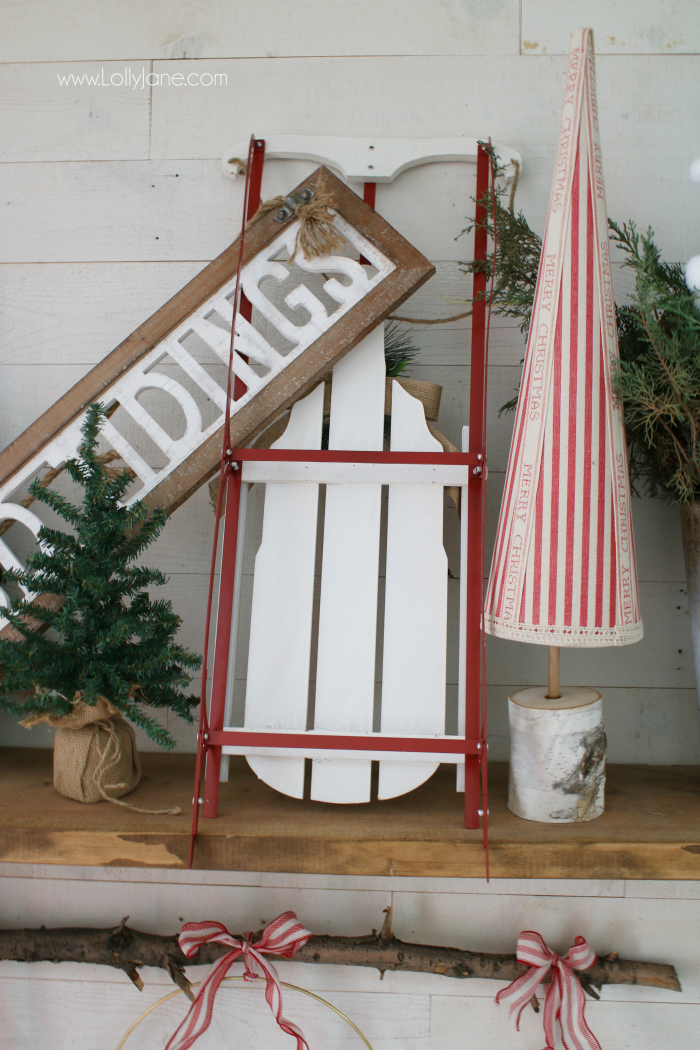 Loving this sled mantel Christmas decor ideas. Use a sled as a focal point for an easy Christmas mantel idea, fill it with a sign, fresh greens in a bucket and small pine trees!