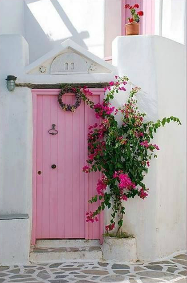 Dying over this bright pink door with a south american feel entryway. Such a pretty combo of the pink and white brick!