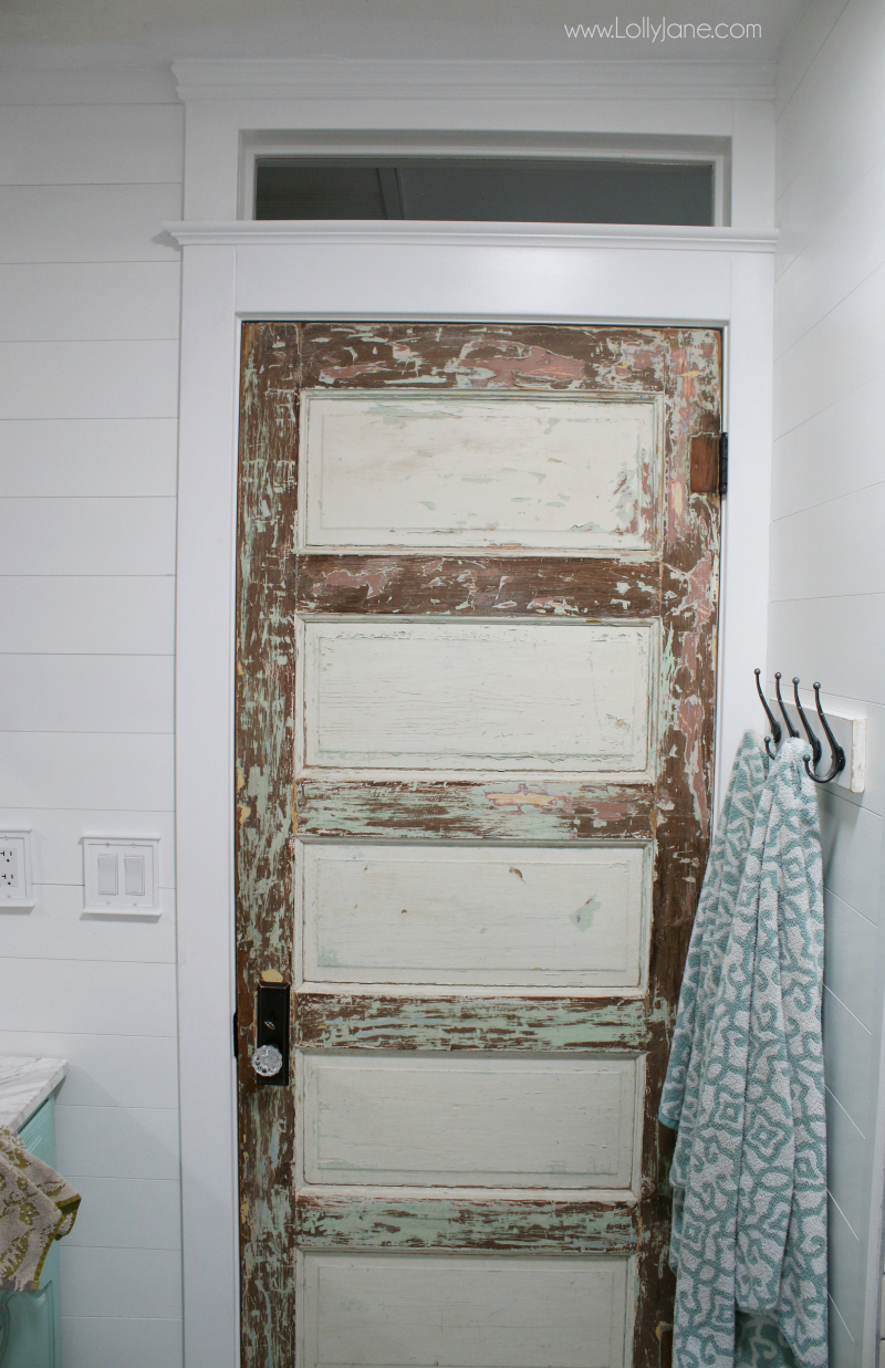 Love this 100 year old vintage bathroom door with pretty farmhouse decor! Lots of inexpensive bathroom renovation tips!