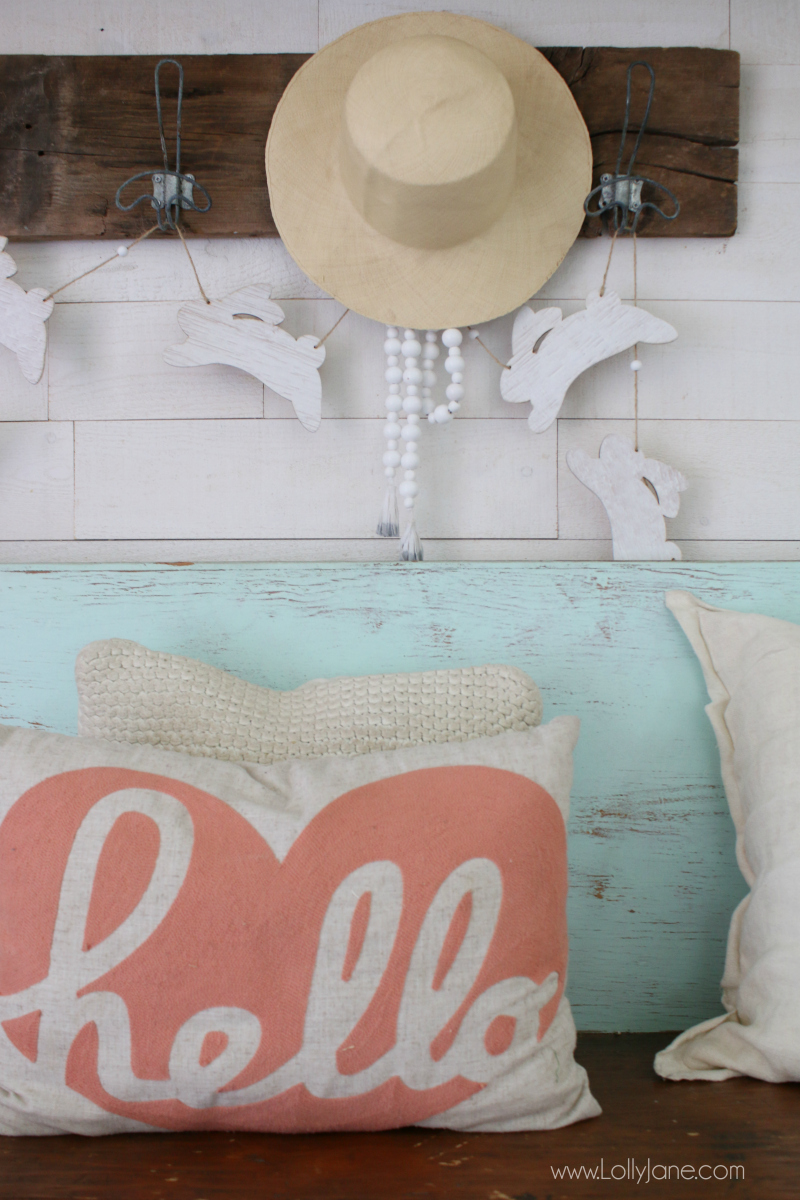 Easy spring entryway decor ideas to spruce up your home! Add white and pink pillows to a bench, hang a wood bunny garland!