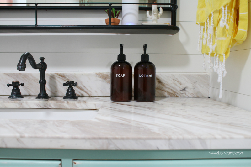 Loving this farmhouse bathroom renovation. These amber bottles are the perfect bathroom accessory to style soap and lotion.