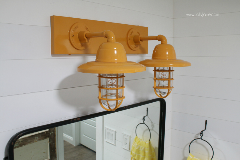 These yellow farmhouse bathroom vanity lights add a pop of color to a muted farmhouse bathroom renovation, so fun!