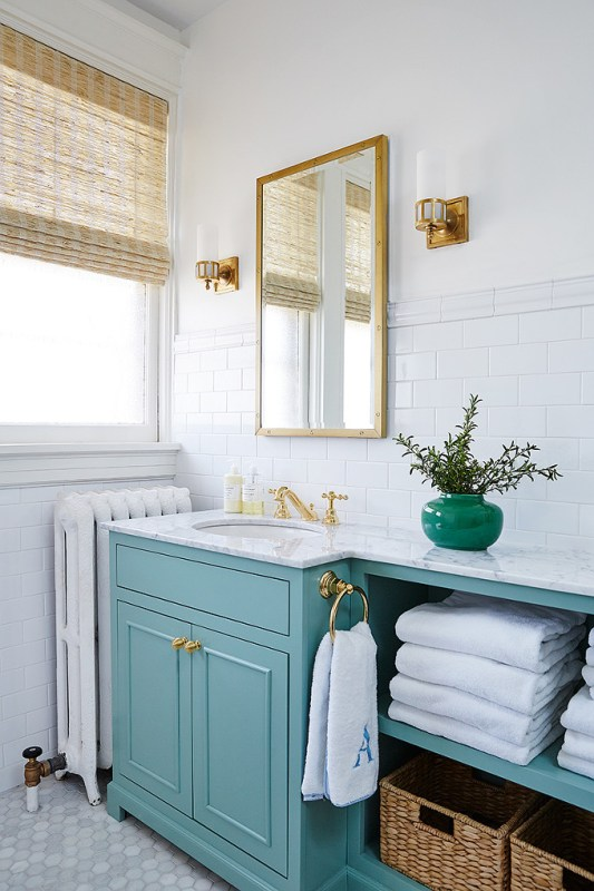 Love this dreamy bathroom decor with its turquoise bathroom vanity and modern brass finishes!