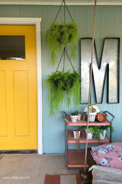 Tips for decorating with hanging plants on a porch. We love ferns and the color and texture they provide when decorating a back porch! #plantdecor #porchdecor #outdoorspaces