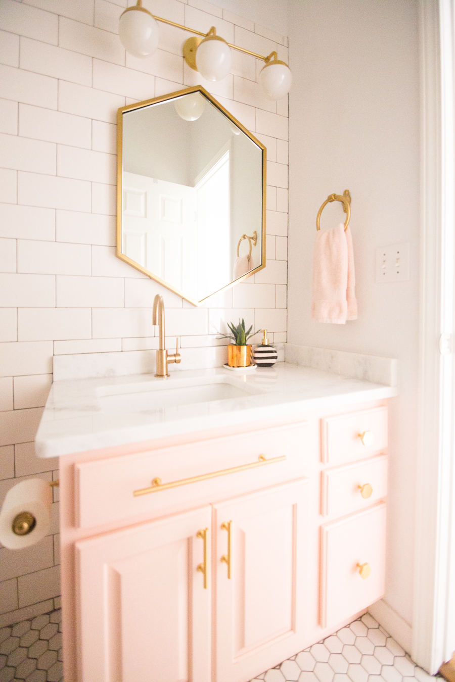 Love this gold hexagon mirror with blush pink cabinets and gold hardware! Such a pretty pink bathroom with gold orb sconces!
