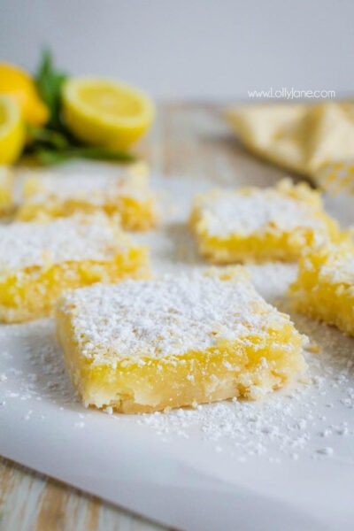 These melt-in-your-mouth lemon bars are bursting with citrus flavor. This is the perfect dessert recipe to whip up for big parties or gatherings any time of year. Family favorite lemon bars recipe, mm! #lemonbars #dessert #lemonrecip