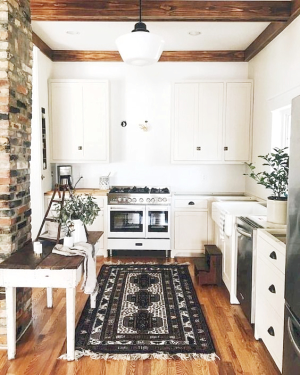 Farmhouse style kitchen rugs are really trendy right now and can really warm up a space. We love this modern farmhouse kitchen rug with white cabinet and wood floors, the patterned rug defines the style of this white farmhouse kitchen. #farmhousekitchen #whitekitchen #farmhousestylerug #modernfarmhouserug #farmhouserug #farmhousekitchenrug