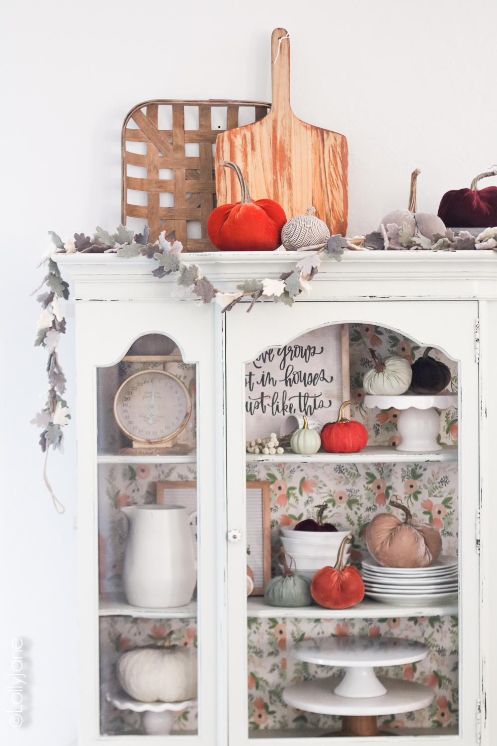 Simple fall decorations... a garland, plush pumpkins, and white dinnerwear make for a bright autumn space! Click to see 5 other fall homes, so beautiful! Add garland and plush pumpkins to your hutch, cabinet, or buffet for instant autumn warmth! #diy #falldecor #homedecor #fallhomedecor