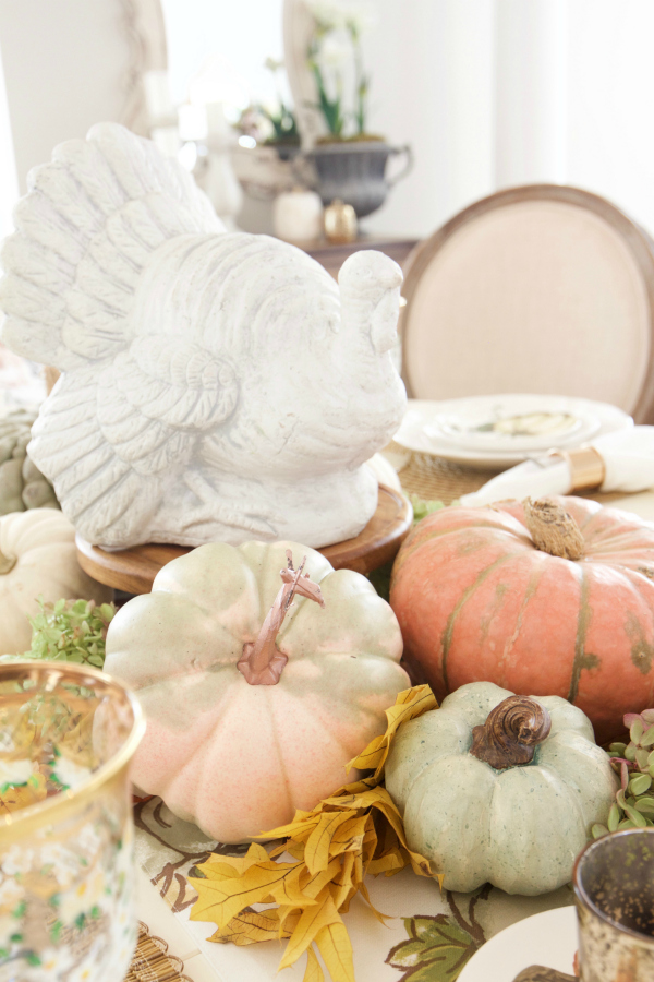 These pumpkins and gourds look so darling with a ceramic vintage style turkey, don't they? How fun to pile more and more gourds and faux flowers to the mix to create the perfect Thanksgiving centerpiece table decoration. #thanksgivingdecor #falldecor #pumpkindecor #thanksgivingcenterpiece