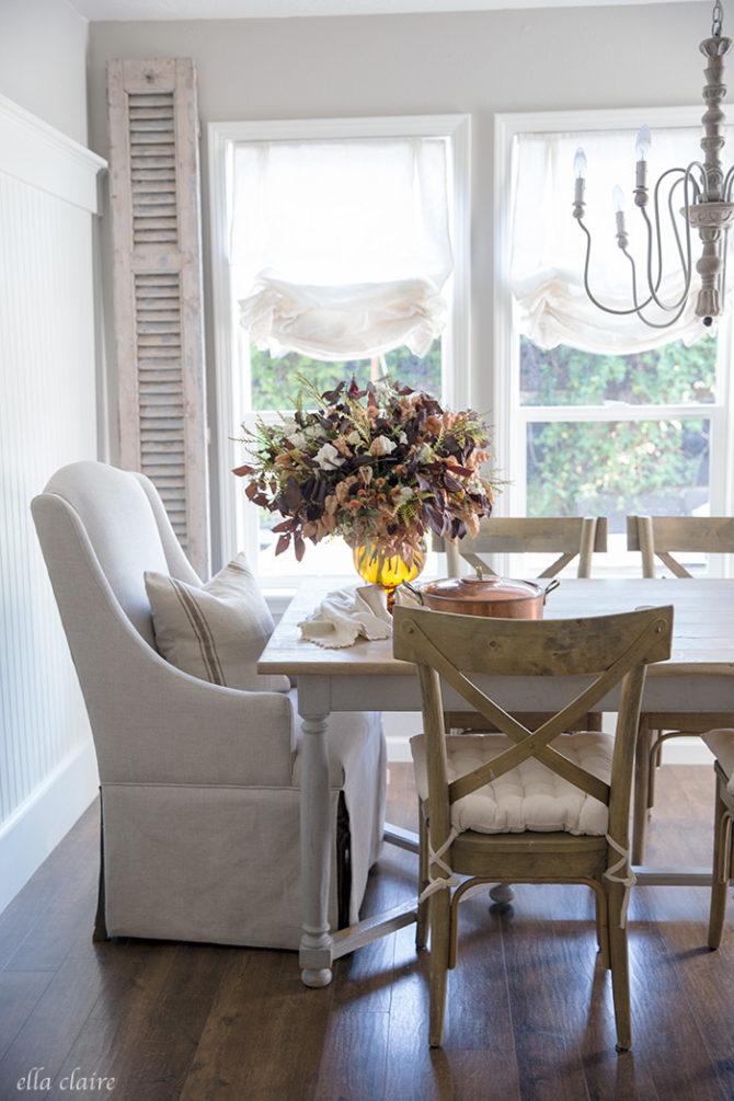 Keep it simple when it comes to Thanksgiving decorating ideas. Lots of white in the room create simple decor so the fall floral centerpiece does the talking. Pair the table with white dishes for stunning Thanksgiving decor! #thanksgivingideas #thanksgiving #thanksgivingdecor