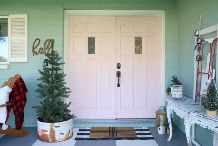 Simple Christmas porch decor on my blue house with pink doors! Looking for easy ways to decorate your porch for Christmas? We've got lots of ideas from several bloggers! #christmashometour #christmasporchideas #christmasdecorations