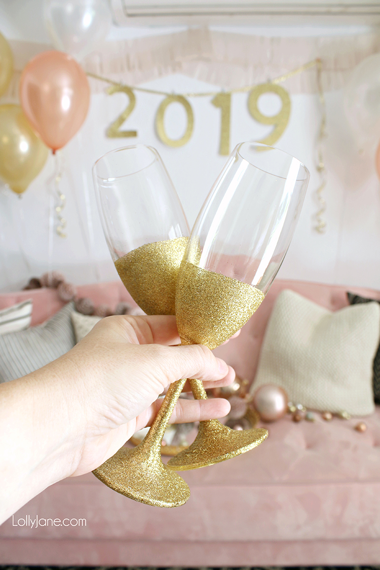 Easy DIY New Years Eve decor! If you can't find these in-store, just spray adhesive on champagne glass + roll in glitter. PERFECT to toast into the New Year! #nye #newyearseve #nyeparty #diy