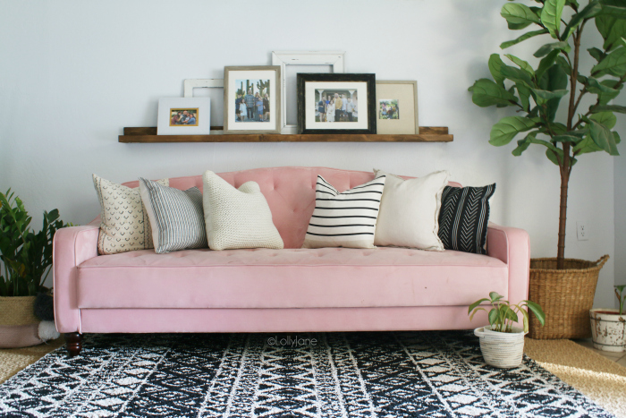 Such fun mid century modern living room furniture! Love this pink velvet tufted couch paired with a tribal rug and plants for pretty boho decor. #eclecticdecor #bohodecor #midcenturymoderndecor