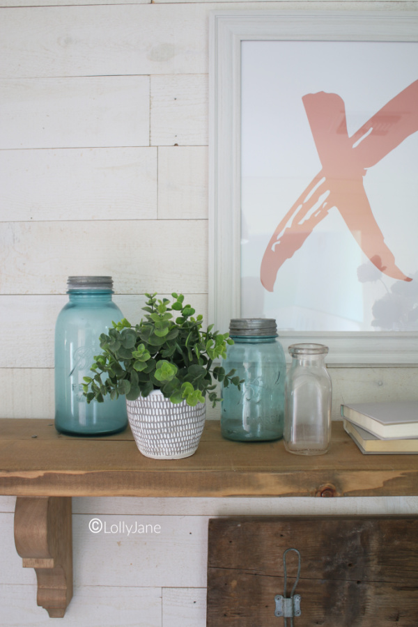 Blue mason jar Valentines Day decor ideas. Love pairing vintage blue jars with flowers to create an easy Valentines Day mantel. Love this Valentines Day entryway decor! #vintagevalentinesday #valentinesdaydecor #vdaydecor #vdaymantel #valentinesdaymantel #bluemasonjarcollection #pinkvaletinesdaydecor #masonjarflowerarrangement #masonjarflowers