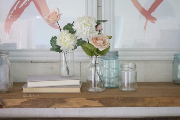 Love these simple mason jar flower arrangements using recycled glass jars and filled with carnations and pink roses. The perfect Valentines Day mantel decor, so easy to put together. #vintagevalentinesday #valentinesdaydecor #vdaydecor #vdaymantel #valentinesdaymantel #bluemasonjarcollection #pinkvaletinesdaydecor #masonjarflowerarrangement #masonjarflowers