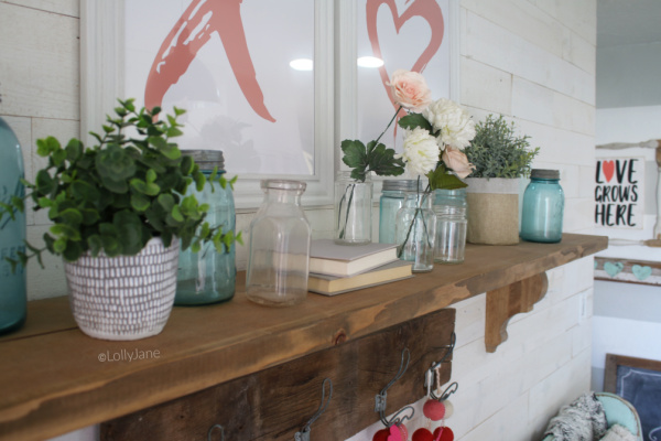 Easy Valentines Day mantel decor ideas | Use these easy to implement decor ideas to put together a simple Valentines Day mantel using aqua jars and pink flowers. #vintagevalentinesday #valentinesdaydecor #vdaydecor #vdaymantel #valentinesdaymantel #bluemasonjarcollection #pinkvaletinesdaydecor #masonjarflowerarrangement #masonjarflowers
