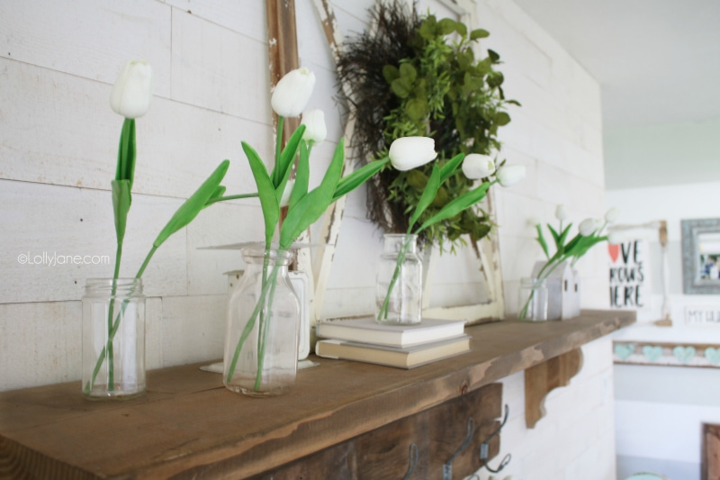 Love these artificial tulips to create easy spring mantle decorations. Adore the old window with a green wreath and old books. #easydecor #springmantel #tulips #decoratingwithtulips #springdecorations