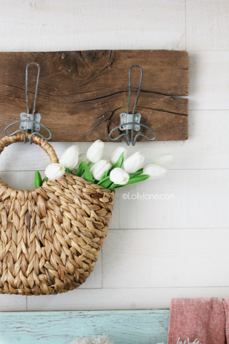 Decorating with tulips in a straw basket is a fun way to welcome spring decor. Put this simple spring mantel together with tulips, glass jars and an old chippy window. #springdecor #tulips #oldwindow #springdecorating #springmantel