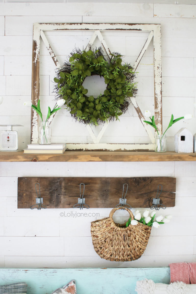 A beautiful vintage inspired, rustic spring mantel featuring an old window, tulips and natural wood accents. Love the vintage inspired farmhouse hooks, too! #springdecor #springmantel #springentryway #springdecorations #tulips