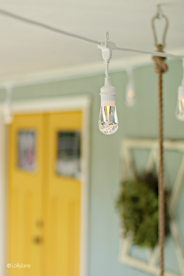 Love these backyard string lights on this cottage porch, so cute. These heavy duty cafe lights don't require you to ever change a light bulb again! #stringlights #cafelights #porchdecor #outdoorlights #outdoorlighting