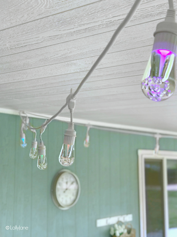 Looking for a cozy backyard with outdoor cafe lights? This cute patio features a modern farmhouse style porch, so cute! #farmhouseliving #cafelights #cozyporch #porchdecor #backporchliving